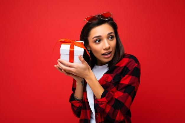 Photo de jeune femme réfléchie positive isolée sur mur de fond rouge
