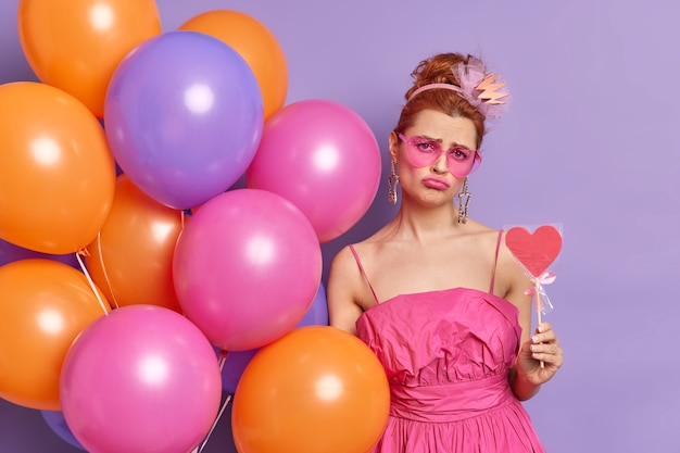 Photo de jeune femme rousse mécontente regarde avec une expression maussade à la caméra détient de délicieux bonbons ballons multicolores pose à l'intérieur sur fond violet