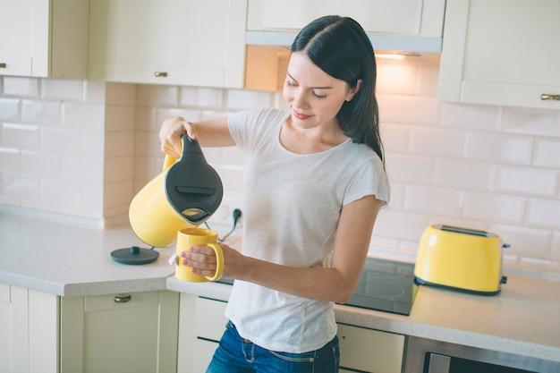 Photo de jeune femme se tient dans la cuisine et verser de l'eau chaude dans une tasse jaune