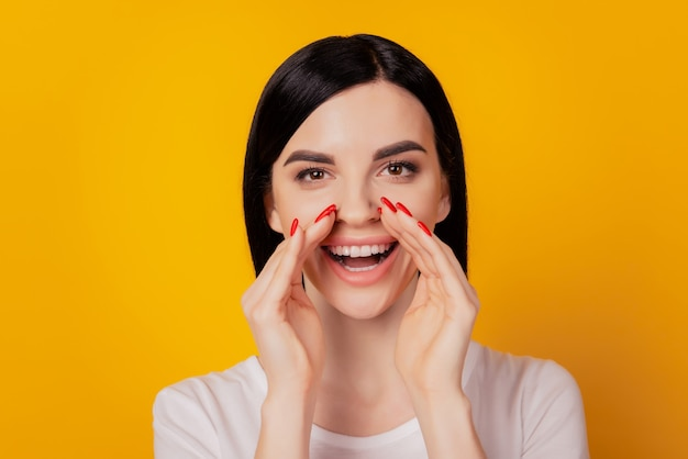 Photo d'une jeune femme séduisante les mains près de la bouche disent dire aux nouvelles crier annonce isolée sur fond de couleur jaune
