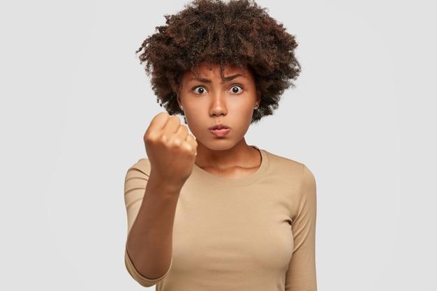 La photo d'une jeune femme sérieuse et stricte domine, montre le poing à la caméra, menace ou met en garde contre quelque chose, se sent en colère