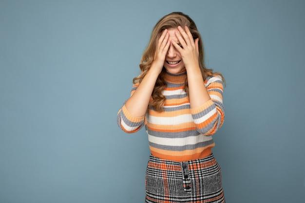 Photo d'une jeune femme souriante heureuse et positive avec des émotions sincères portant des vêtements élégants isolés sur fond avec espace de copie et couvrant les yeux.