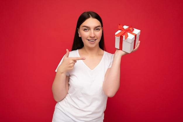 Photo de jeune femme souriante positive isolée sur mur de fond rouge portant