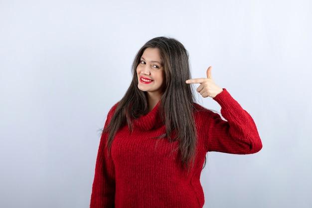 Photo d'une jeune femme souriante en pull rouge pointant vers l'extérieur