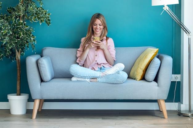 Photo d'une jeune femme souriante utilisant son téléphone portable alors qu'elle était assise sur un canapé à la maison.