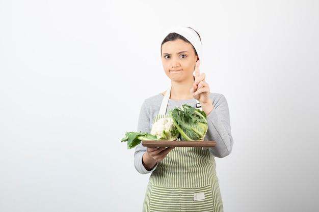 Photo d'une jeune femme en tablier tenant une assiette en bois avec des choux-fleurs