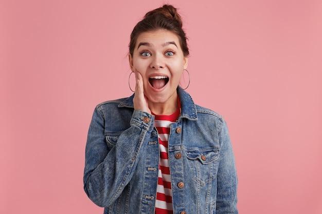 Photo d'une jeune femme avec des taches de rousseur, met la main à la face et veut vous dire la nouvelle choquante, vêtue d'une veste en jean t-shirt rayé, regardant la caméra, isolée sur un mur rose.