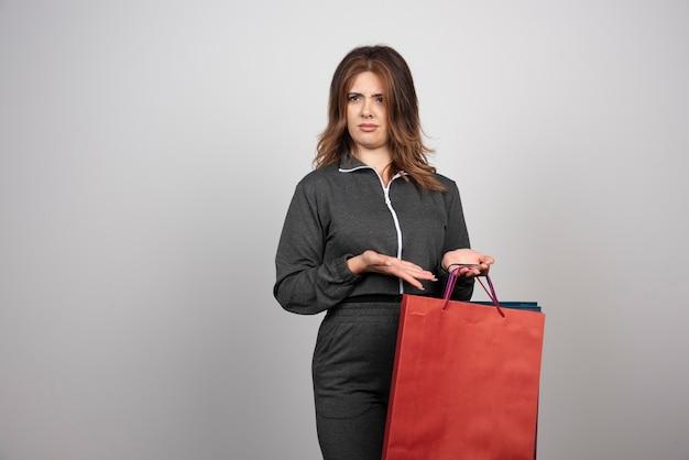 Photo de jeune femme tenant des sacs à provisions.