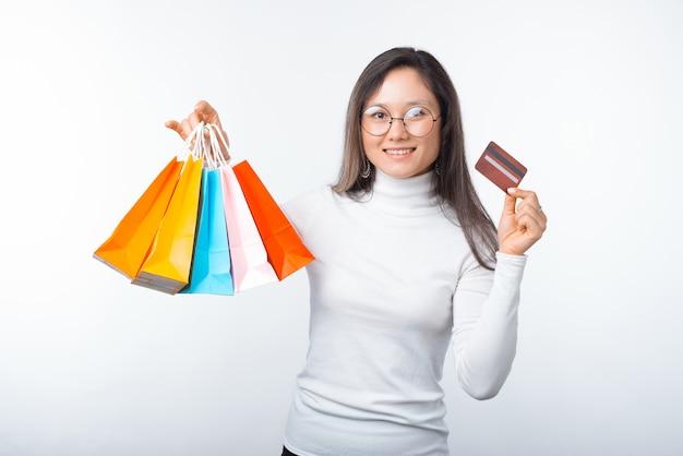 Photo de jeune femme tient des sacs à provisions et une carte de crédit. achetez en ligne et payez par carte.