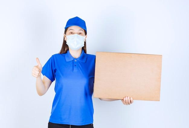 Photo de jeune femme en uniforme avec boîte en papier montrant le pouce vers le haut.