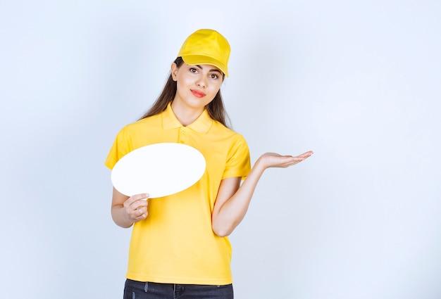 Photo de jeune femme en uniforme jaune tenant une bulle de dialogue vide sur un mur blanc.