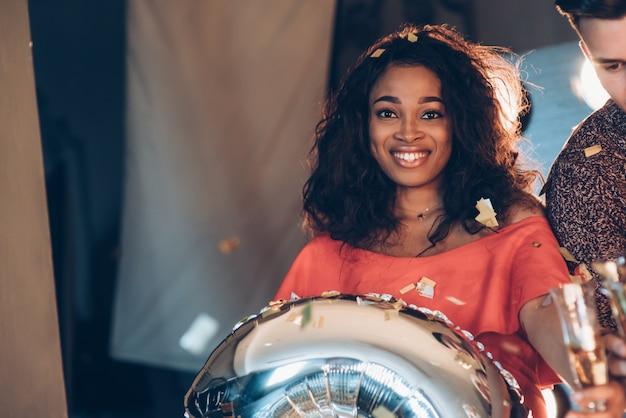 Photo de jeune fille afro-américaine avec ballon d'argent dans les mains, debout à l'intérieur près de l'ami et souriant. confetti dans l'air