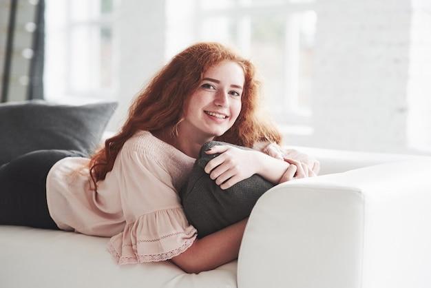 Photo de la jeune fille allongée sur le canapé blanc et souriante