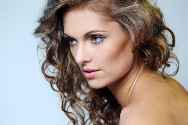 Photo de jeune fille brune avec une peau parfaite sur fond gris