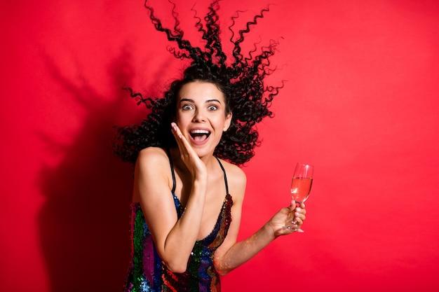 Photo de jeune fille charmante tenir un verre à vin bouche ouverte paume joue porter une robe brillante fond de couleur rouge isolé