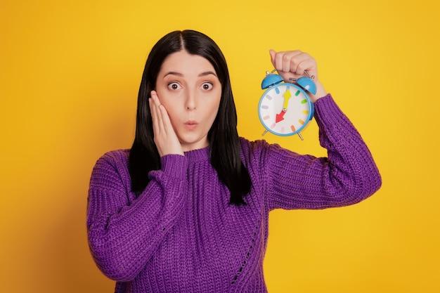 Photo de jeune fille choquée handtouch joue tenir réveil minuterie raté isolé sur fond de couleur jaune