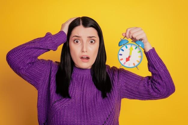 Photo d'une jeune fille choquée surprise de la tête tactile d'échéance de l'horloge d'alarme isolée sur fond de couleur jaune