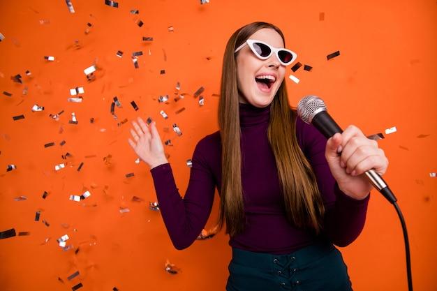 Photo d'une jeune fille cool hipster profitez d'une soirée karaoké chanter une chanson mic porter un cavalier violet violet isolé sur des confettis voler automne brillant fond de couleur