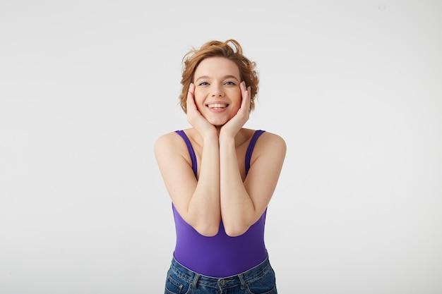 Photo de jeune fille mignonne aux cheveux courts porte une chemise violette, touche le visage avec ses mains, regarde et démontre la beauté naturelle, sourit largement, se dresse sur un mur blanc.