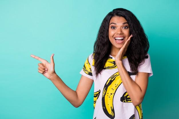 Photo de jeune fille mignonne joue du bras indiquer l'espace vide du doigt porter un t-shirt imprimé banane isolé sur fond de couleur turquoise
