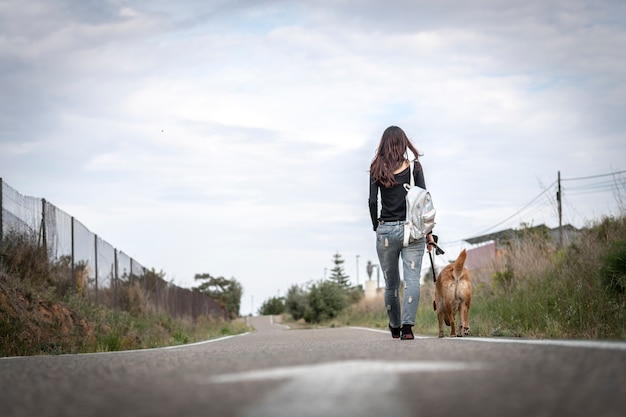 Photo d'une jeune fille promenant son chien