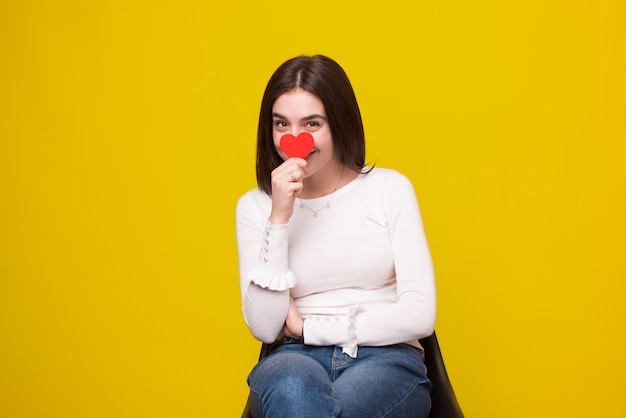 Photo d'une jeune fille souriante joyeuse se cache son visage derrière un coeur rouge sur l'espace jaune.