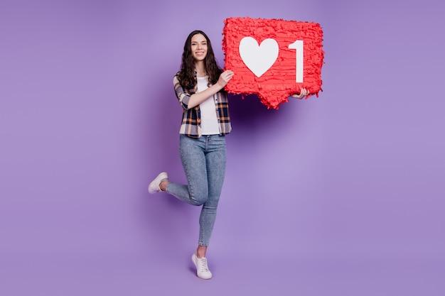 Photo de jeune fille tenir coeur pinata papier comme icône de réaction populaire isolé sur fond de couleur violet
