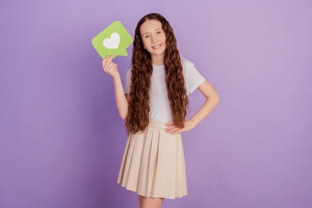 Photo de jeune fille tenir l'icône du cœur comme isolé sur fond violet