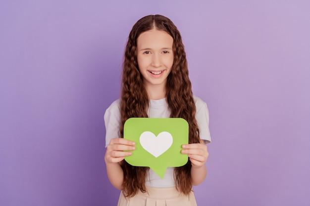 Photo de jeune fille tenir l'icône de réaction comme isolé sur fond violet