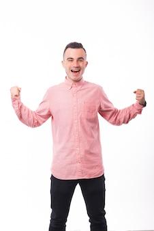 Photo d'un jeune gagnant, debout sur un espace blanc et célébrant avec les mains levées