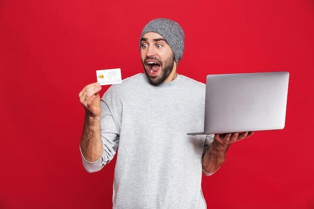 Photo de jeune homme de 30 ans en tenue décontractée tenant une carte de crédit et un ordinateur portable en argent isolé