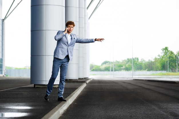 Photo de jeune homme d'affaires aux cheveux roux attraper la voiture et parler au téléphone