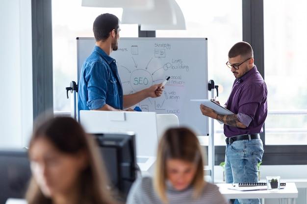 Photo d'un jeune homme d'affaires pointant sur un tableau blanc tout en discutant avec son collègue de leur nouveau projet dans le bureau de démarrage moderne.
