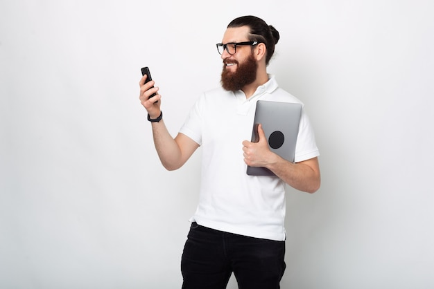 Photo d'un jeune homme à la barbe en t-shirt blanc utilisant un smartphone et tenant un ordinateur portable
