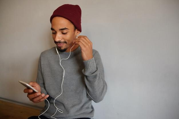 Photo de jeune homme barbu attrayant positif à la peau foncée insérant des oreillettes dans son oreille et tenant un téléphone portable, regardant gaiement à l'écran alors qu'il était assis sur un mur blanc