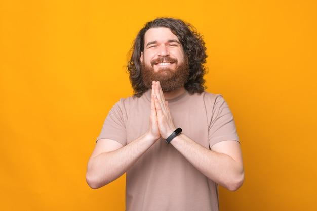 Photo de jeune homme barbu aux longs cheveux bouclés faisant un geste s'il vous plaît