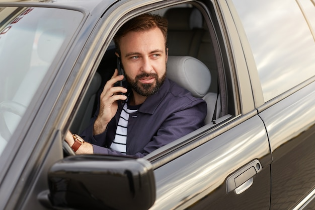 Photo d'un jeune homme barbu beau succès vêtu d'une veste bleue et d'un t-shirt rayé, assis derrière le volant de la voiture, appelle un ami sur son téléphone portable, regarde ailleurs.