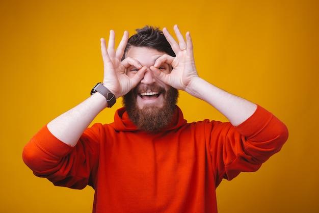 Photo d'un jeune homme barbu sur un espace jaune excité en gardant un geste correct sur les yeux.