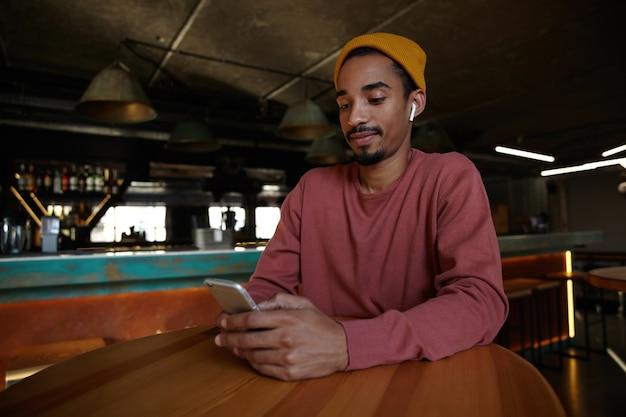 Photo de jeune homme barbu à la peau sombre tenant le smartphone dans les mains et le tenant sur le comptoir, gardant les lèvres pliées tout en regardant à l'écran, assis sur l'intérieur du bar