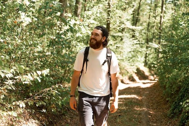 Photo de jeune homme barbu, randonnée en forêt pendant l'heure d'été, concept de voyage.