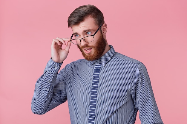 Photo d'un jeune homme barbu séduisant, regardant avec désapprobation à travers ses lunettes, un collègue a commis une stupide erreur de travail. isolé sur fond rose.