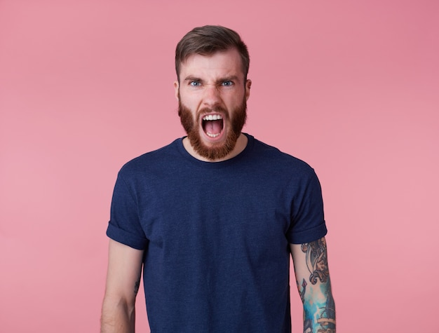 Photo d'un jeune homme barbu tatoué en t-shirt blanc, hurlant et ressentant une forte douleur et en colère, se dresse sur fond rose.