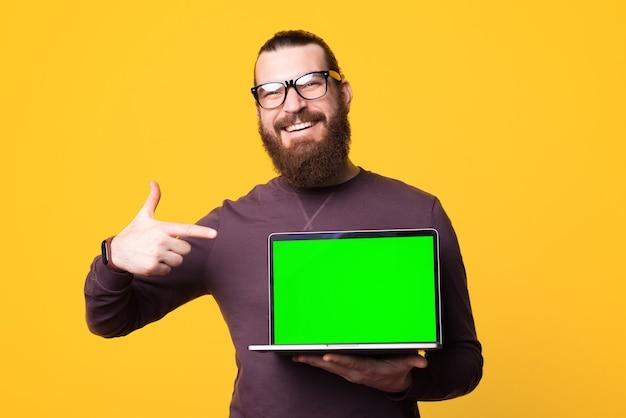 Photo d'un jeune homme barbu tenant un ordinateur sourit et le pointe du doigt
