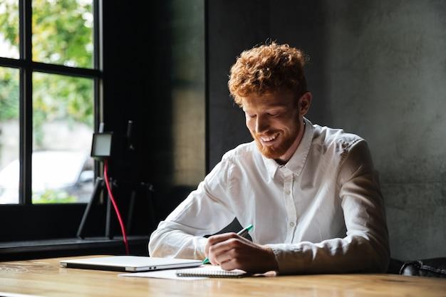 Photo de jeune homme barbu à tête de lecture souriante, prenant des notes, assis au café