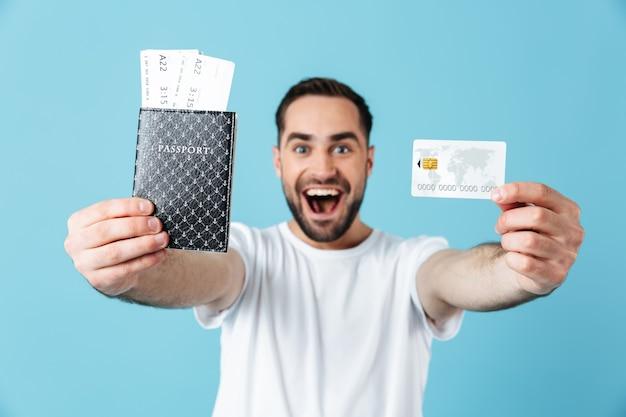 Photo d'un jeune homme brune portant un t-shirt basique souriant tout en tenant des billets de voyage avec passeport et carte de crédit isolés sur bleu