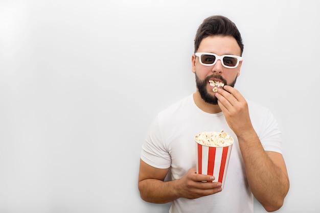 Photo de jeune homme debout et regardant. sa bouche est pleine de pop-corn. il tient un petit seau de maïs croquant et continue de manger.