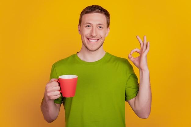 Photo de jeune homme heureux sourire positif boire une tasse de café montrer ok bien signe isolé sur fond de couleur jaune