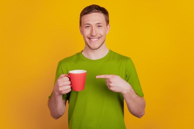 Photo de jeune homme heureux sourire positif point doigt tasse de café conseil ad isolé sur fond de couleur jaune