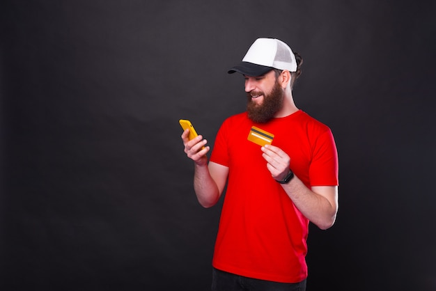 Photo de jeune homme joyeux hipster barbu en t-shirt rouge acheter quelque chose en ligne avec carte de crédit et smartphone