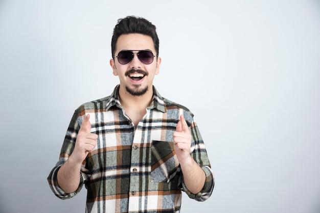 Photo de jeune homme à lunettes noires debout sur un mur blanc.